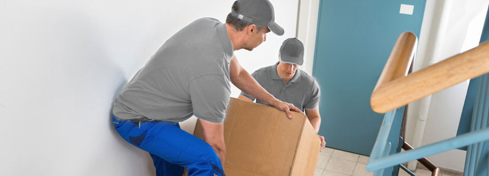 Two-Classic-Moves-Movers-Carrying-Heavy-Box-Upstairs