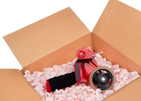 A box full of protective packaging peanuts and a tape dispenser ready to be sealed up for shipping.